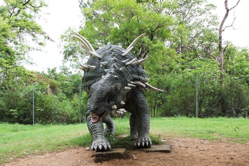 As esculturas as mais bonitas do dinossauro colocadas na fotografia do parque da selva foto de stock royalty free