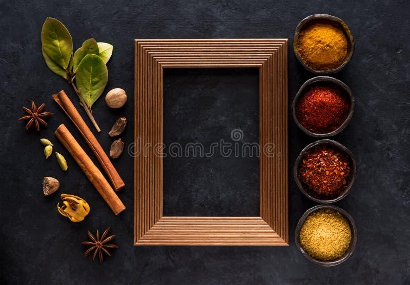 As especiarias, picante indianos e tempero em umas bacias e esvaziam o quadro de madeira para o texto no fundo concreto preto, foto de stock