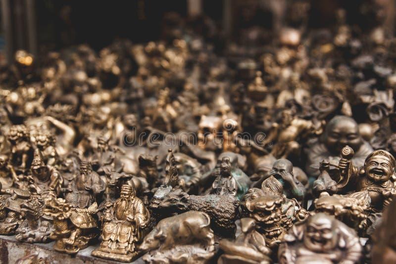 As estátuas e as estatuetas pequenas do ouro em um mercado param em Hong Kong foto de stock