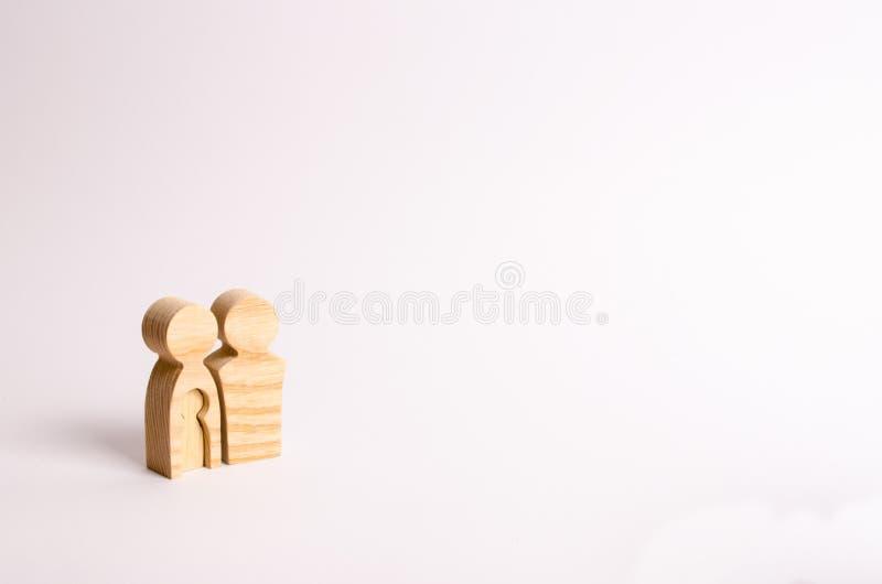 As estatuetas de madeira dos pais estão em um fundo branco Conceito da gravidez, família nova Planear para a família foto de stock royalty free