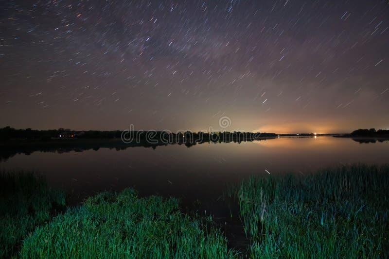 As estrelas brilhantes brilham e voam sobre um lago grande do campo com os arbustos do junco em uma obscuridade morna da noite da imagens de stock royalty free
