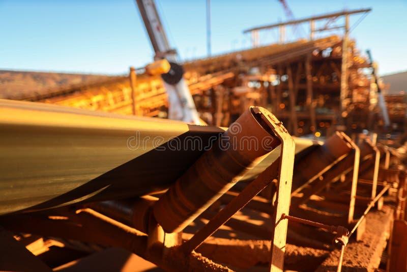 As estruturas da correia transportadora e dos rolos alinham seu minério de ferro de transferência no local material da mina da co imagem de stock