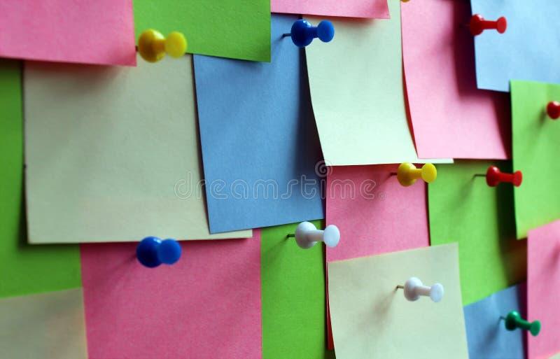 As etiquetas coloridos são fixadas com os botões na placa fotos de stock
