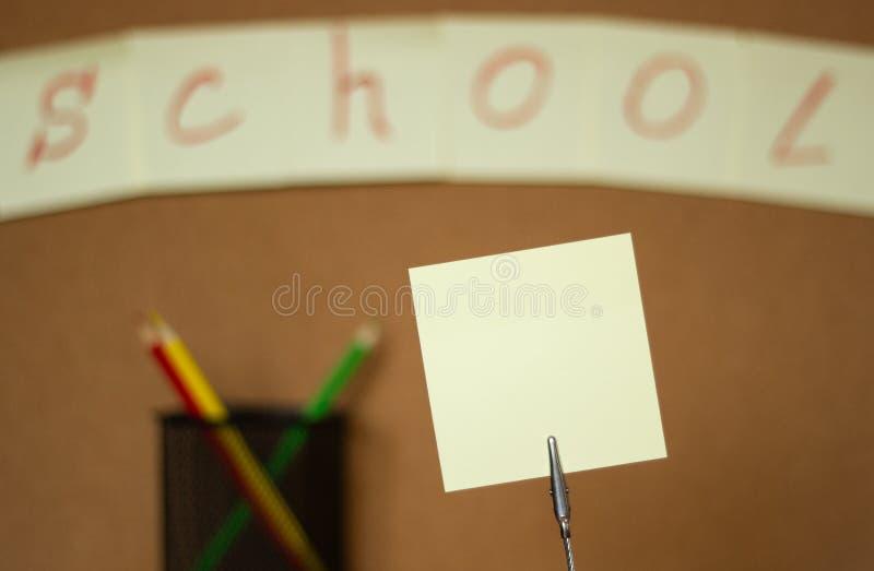 As etiquetas e os lápis coloridos em um fundo borrado de uma cortiça embarcam com uma inscrição fotos de stock royalty free