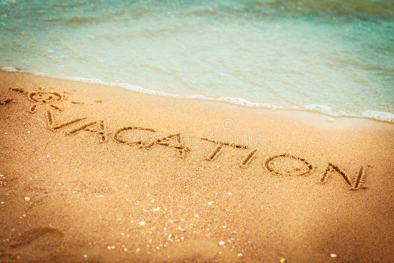 As férias da palavra escritas na areia em uma praia imagens de stock royalty free
