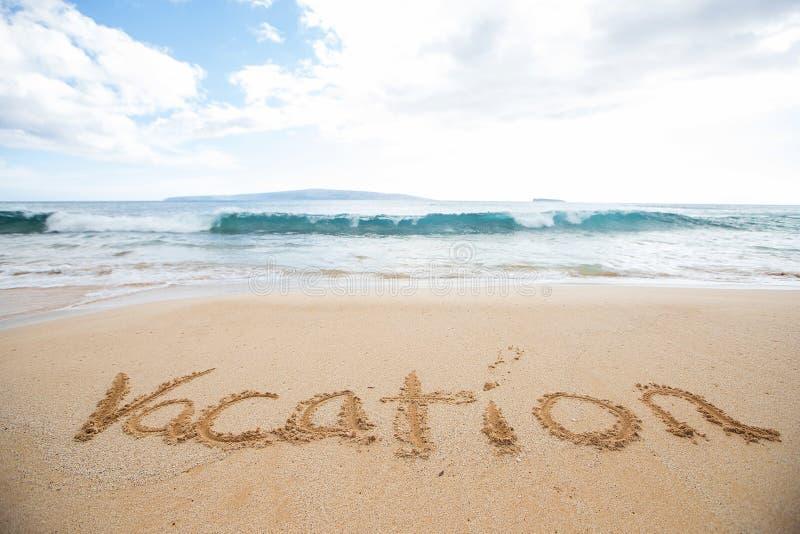 As férias da palavra escritas na areia em uma praia tropical da ilha imagem de stock