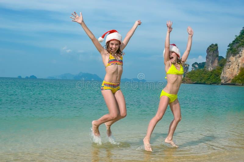 As férias em família em feriados do Natal e do ano novo, crianças têm o divertimento na praia, crianças em chapéus de Santa imagens de stock royalty free