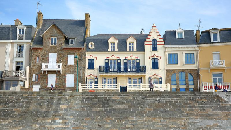 As fachadas coloridas da casa ao longo de Sillon encalham com os povos que andam ao longo do digue de Rochebonne da esplanada fotos de stock