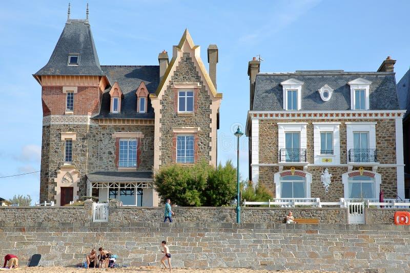 As fachadas coloridas da casa ao longo de Sillon encalham com os povos que andam ao longo do digue de Rochebonne da esplanada e o imagem de stock