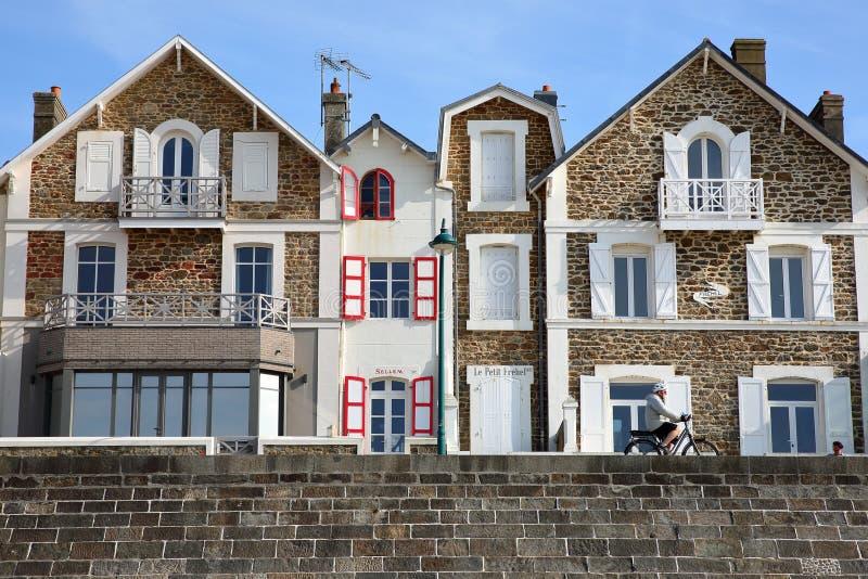 As fachadas coloridas da casa ao longo de Sillon encalham com um ciclismo do homem ao longo do digue de Rochebonne da esplanada fotos de stock royalty free