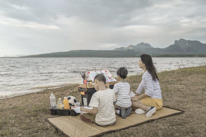 As famílias ensinam crianças pintar, feriados da família com natureza foto de stock royalty free