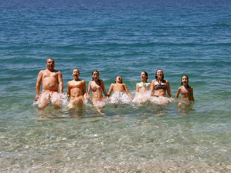 As famílias grandes, felizes saltam no mar foto de stock royalty free