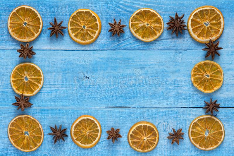 As fatias alaranjadas secadas com partes de anis de estrela, formam um quadro em uma tabela de madeira fotos de stock royalty free