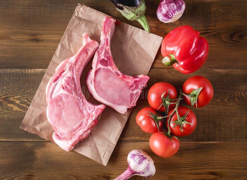As fatias da carne crua em um fundo rústico de madeira com os vegetais orgânicos frescos alho, tomates salpicam cozinhando o almo fotos de stock