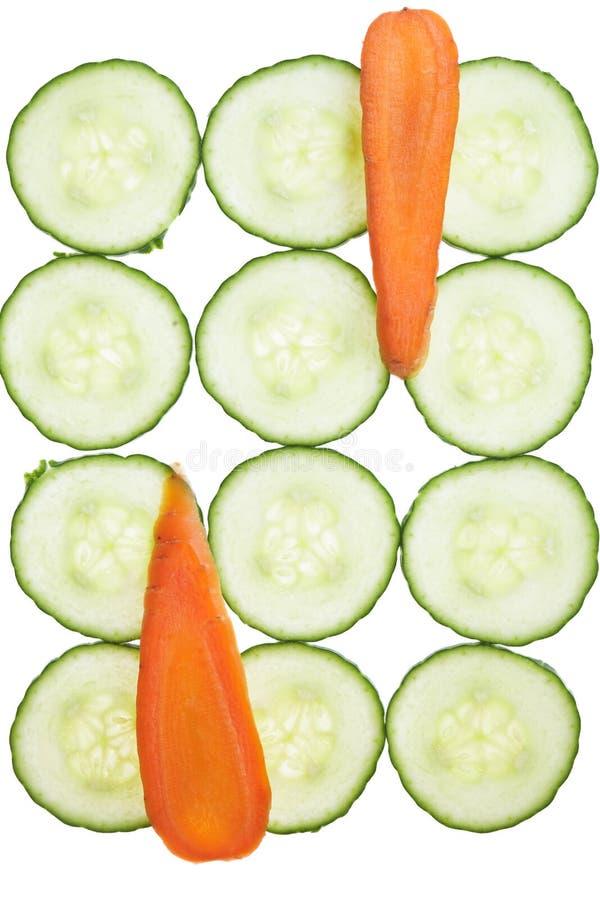 As fatias da cenoura e do pepino arrranged em um teste padrão. fotos de stock