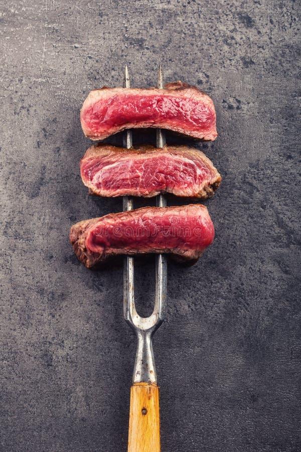 As fatias de bife do lombo na carne bifurcam-se no fundo concreto fotografia de stock