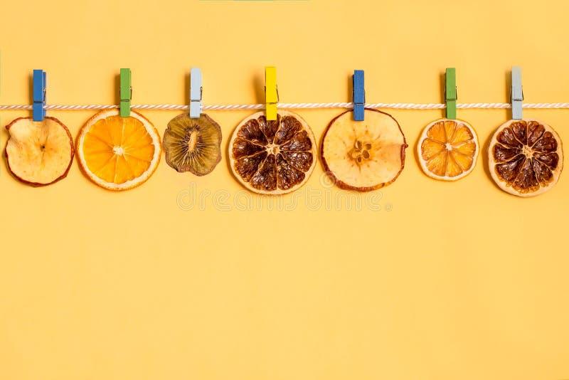 As fatias de fruto secaram na corda com pregadores de roupa fotos de stock