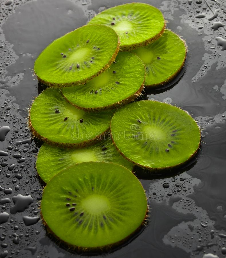 As fatias de quivi na água deixam cair em um fundo preto Conceito do fruto fotografia de stock