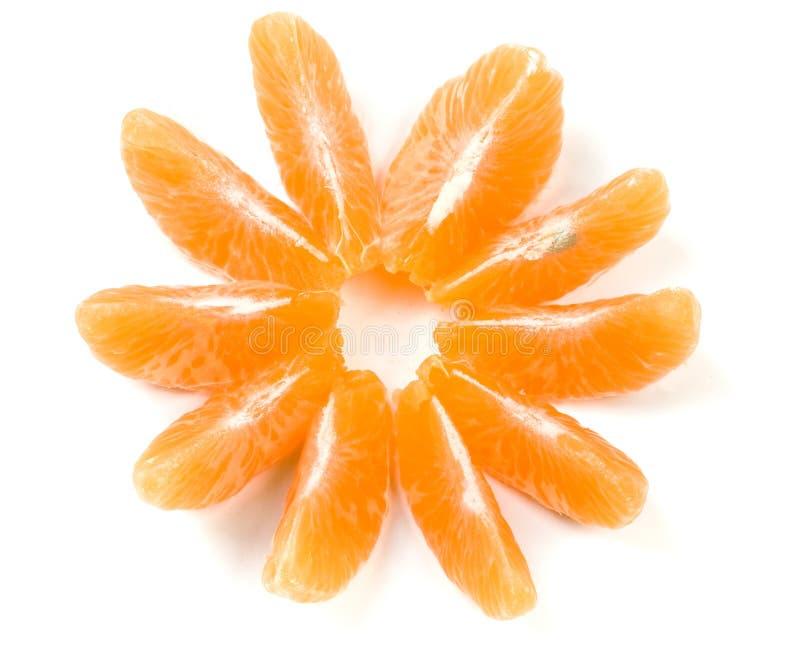 As fatias de tangerina divulgaram no formulário uma flor no fundo branco fotografia de stock