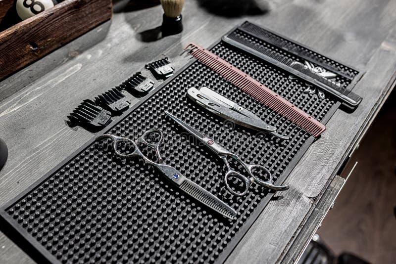 As ferramentas da mentira do cabeleireiro em uma esteira preta no desktop imagem de stock