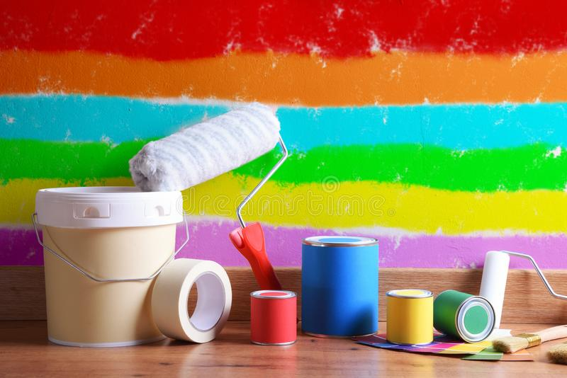 As ferramentas de pintura no assoalho de parquet com parede pintaram várias cores foto de stock