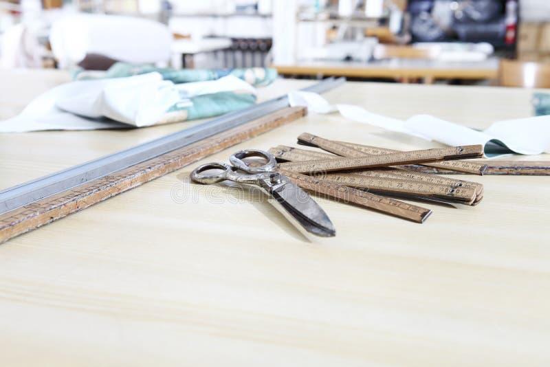 As ferramentas do alfaiate, tesouras velhas, medidor de madeira e régua na tabela de trabalho de alfaiate foto de stock royalty free