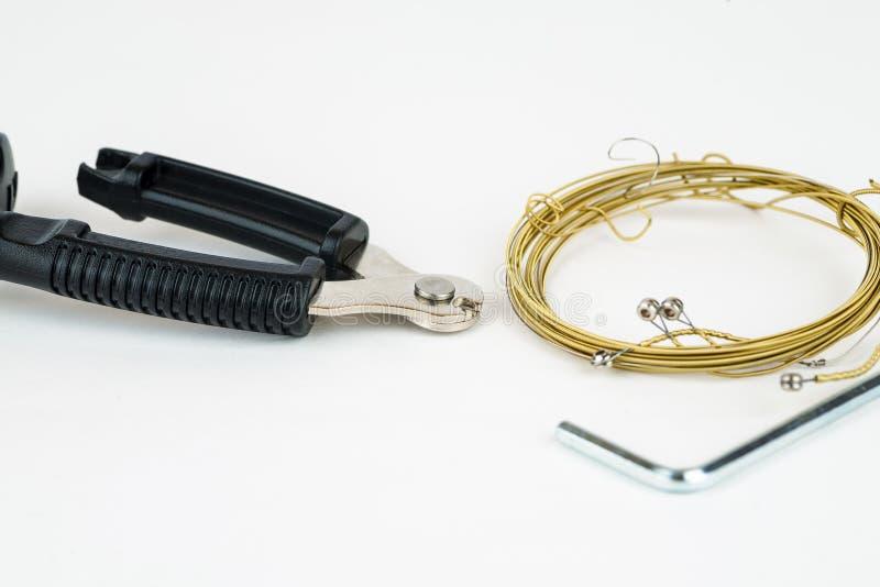 As ferramentas para cordas da guitarra acústica mudam em um fundo branco fotos de stock royalty free