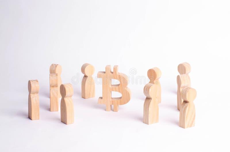 As figuras de madeira dos povos estão estando perto de um bitcoin em um fundo branco Moeda cripto, tecnologia do blockchain imagens de stock