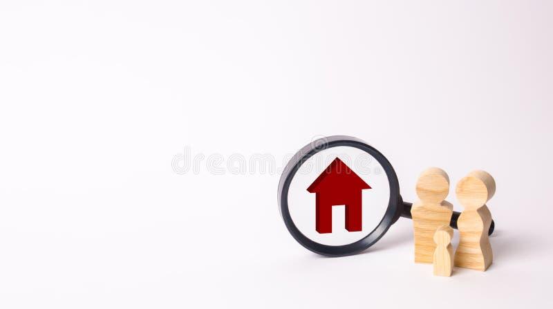 As figuras de madeira dos povos estão perto da lupa Família nova à procura do alojamento disponível novo Compra ou aluguer ho fotos de stock royalty free