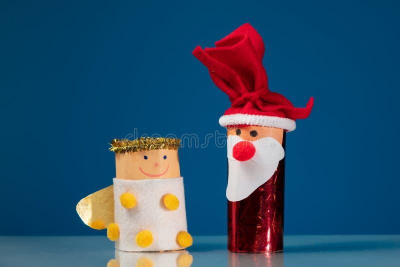 As figuras de Santa Claus e de um anjo fizeram de um rolo do papel higiênico por uma criança fotografia de stock royalty free