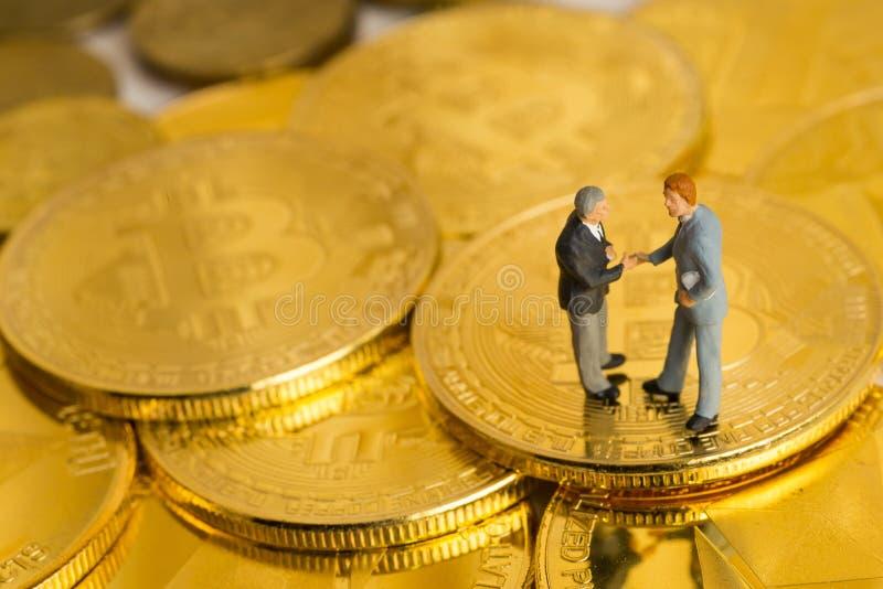As figuras diminutas de dois homens de negócios concordaram um negócio imagem de stock