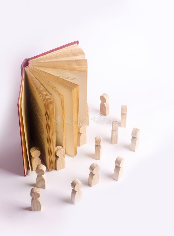As figuras diminutas dos povos saem do livro no mundo real O livro vem vivo, os caráteres sai do livro foto de stock