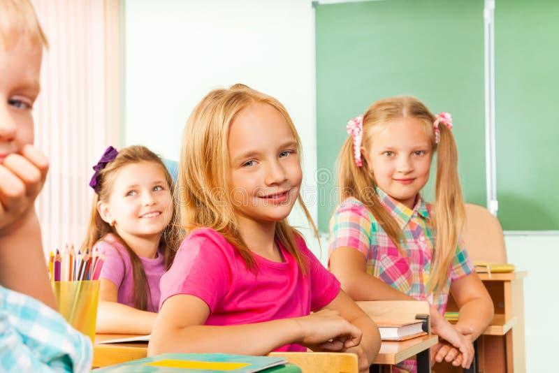 As fileiras da mesa com alunos olham o assento reto girado fotografia de stock royalty free