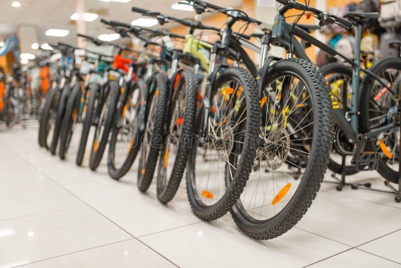 As fileiras de bicicletas da montanha nos esportes compram, ninguém imagem de stock royalty free