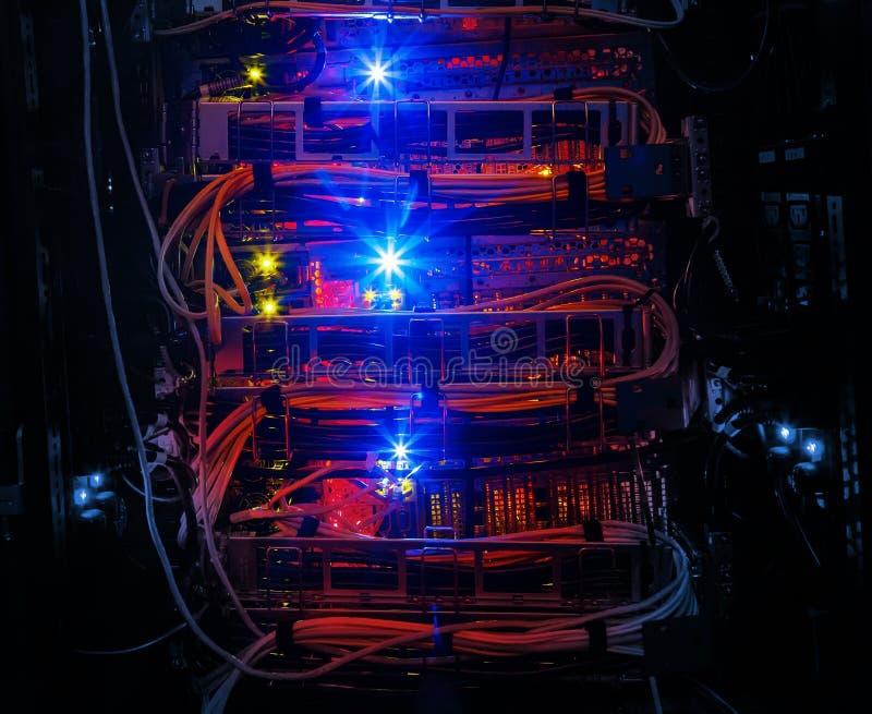 As fileiras de cabos vermelhos da rede conectaram ao cubo do roteador e do interruptor na sala do servidor no centro de dados do  fotografia de stock