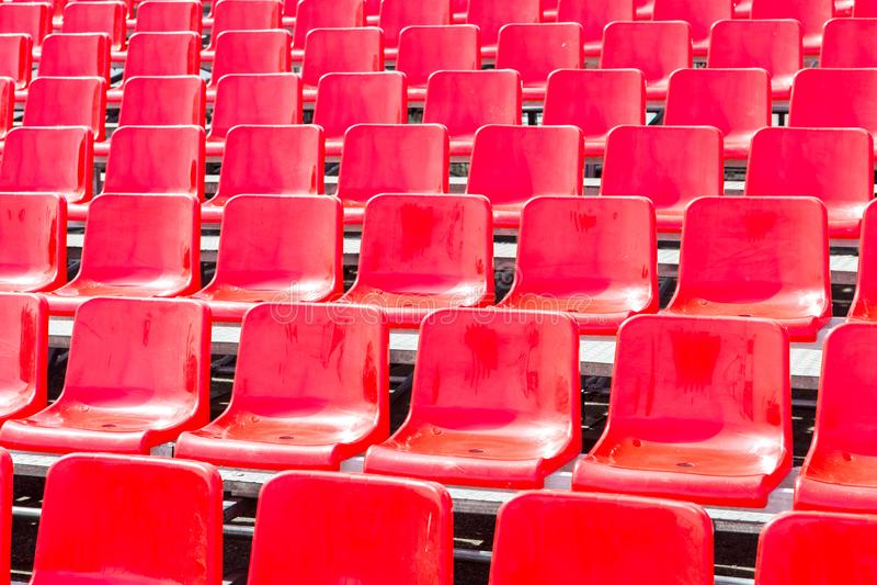 As fileiras esvaziam assentos plásticos vermelhos em um estádio imagem de stock