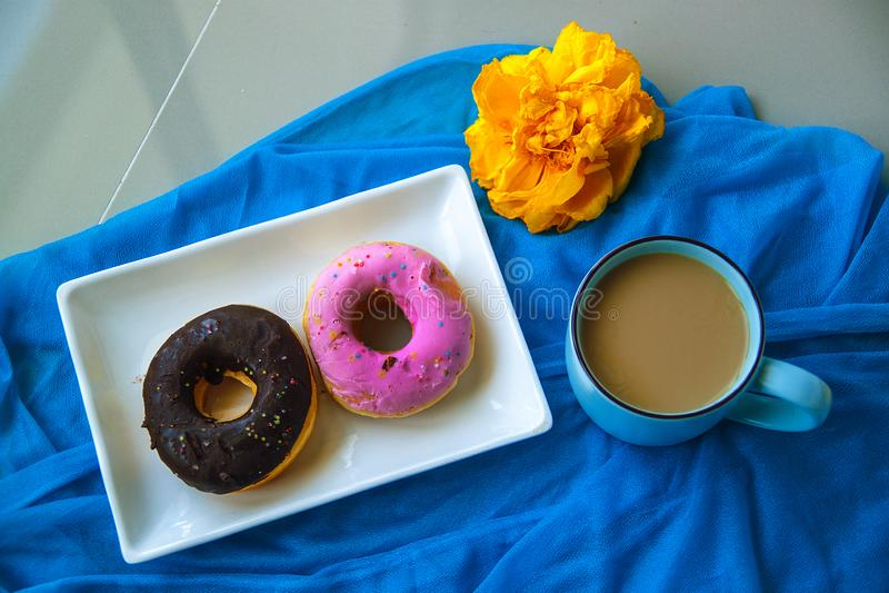 As filhóses vitrificadas com açúcar e chocolate polvilham e uma xícara de café fotografia de stock