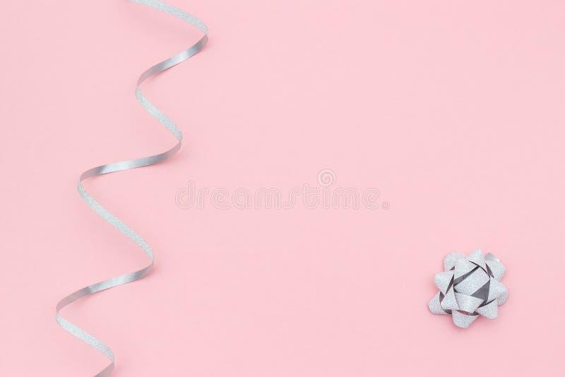 As fl?mulas de prata serpenteiam e curvam-se no fundo cor-de-rosa no estilo m?nimo Decora??es do conceito para a celebra??o, part fotografia de stock royalty free