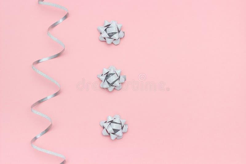 As flâmulas de prata serpenteiam e curvas no fundo cor-de-rosa no estilo mínimo Decorações do conceito para a celebração, p foto de stock