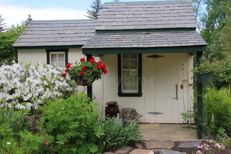 As flores coloridas brilhantes decoram esta casa de campo pequena fotografia de stock royalty free