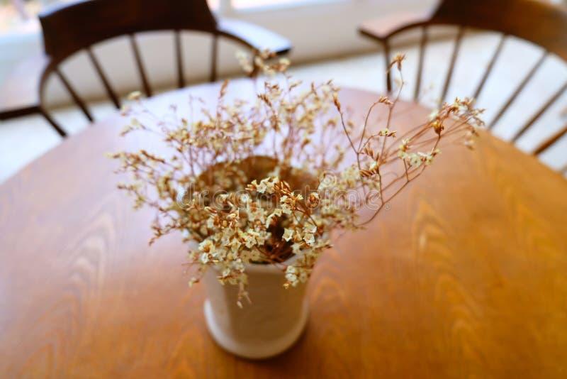 As flores da decoração são coloridas belamente na tabela em uma cafetaria imagens de stock