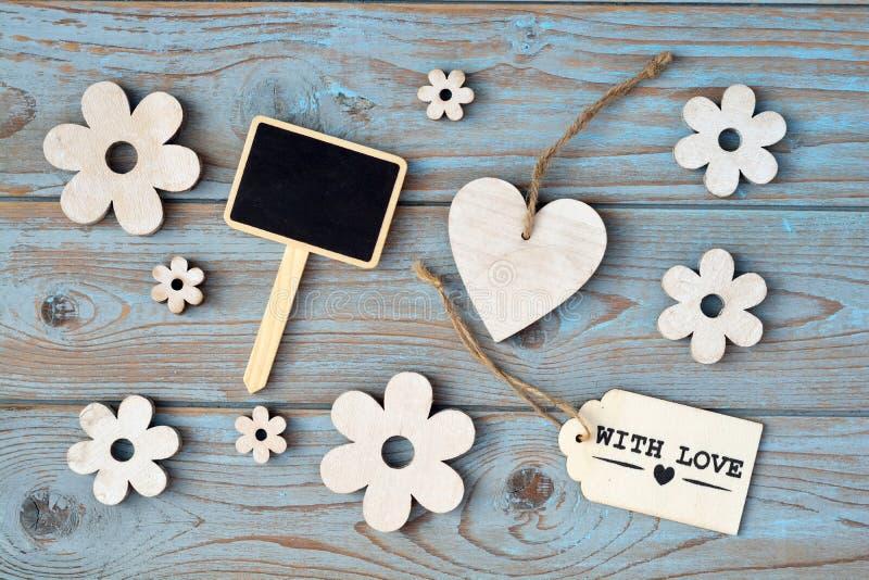 As flores de madeira, coração, placa de giz preta e com etiqueta do amor em um cinza azul ataram o fundo de madeira velho com dis foto de stock