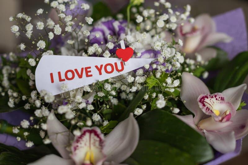 As flores e o cartão com inscrição amam-no Fundo do dia de Valentim e mensagem do amor Conceito da confissão do amor feliz fotografia de stock