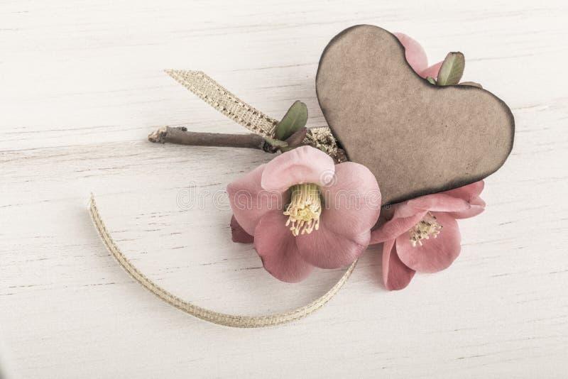 As flores e o coração da mola deram forma ao cartão no fundo de madeira fotos de stock