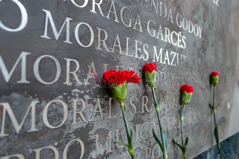 As flores memoráveis colocam contra os nomes das vítimas imagem de stock