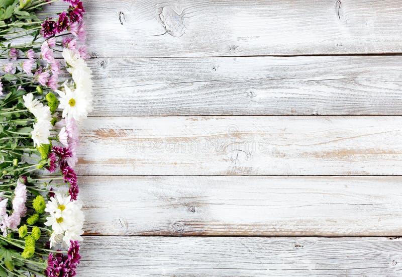 As flores misturadas que formam a beira esquerda no branco resistiram ao varrão de madeira foto de stock
