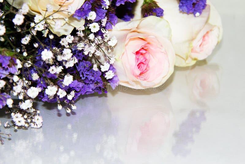 As flores roxas pequenas misturaram dentro com a respiração branca do ` s do bebê e as rosas cor-de-rosa em um ramalhete imagens de stock