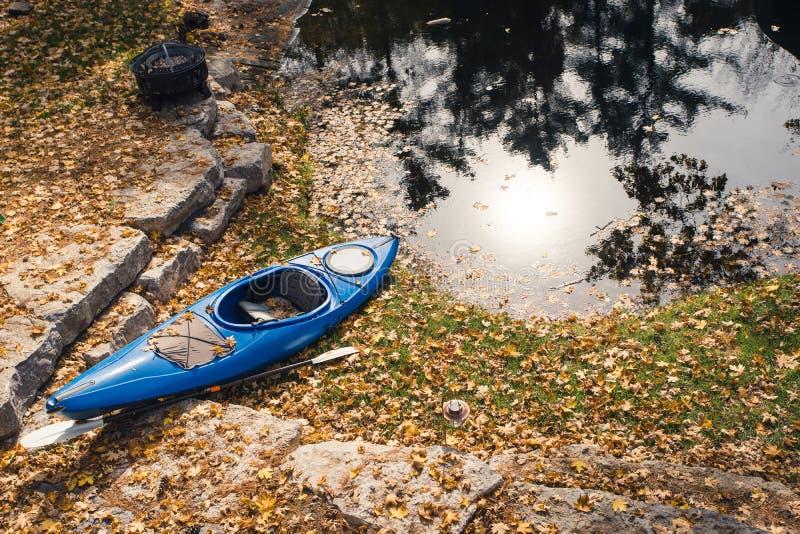 As folhas de outono recolhem em um caiaque azul foto de stock