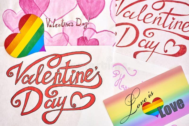 As folhas de papel com cumprimentos para o dia de Valentim, sobre o coração do arco-íris LGBT e um sinal com o amor da inscrição  imagens de stock royalty free
