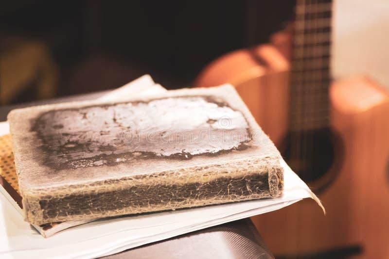As folhas e o livro na tampa velha na guitarra do fundo fotos de stock royalty free